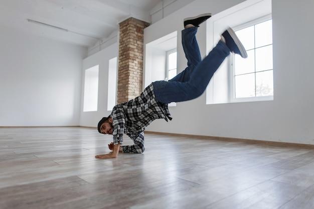 Młody stylowy tancerz facet z dżinsami i koszulą taniec w jasnym studio tańca