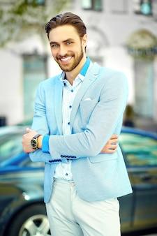 Młody stylowy ufny szczęśliwy przystojny uśmiechnięty biznesmena modela mężczyzna w błękitnego kostiumu sukiennym stylu życia na ulicie