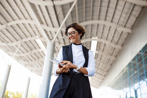 Młody sukcesy bizneswoman patrząc na tablet, stojąc w pobliżu centrum biznesowego