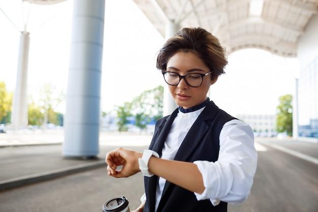 Młody sukcesy bizneswoman patrząc na zegarek, stojąc w pobliżu centrum biznesowego