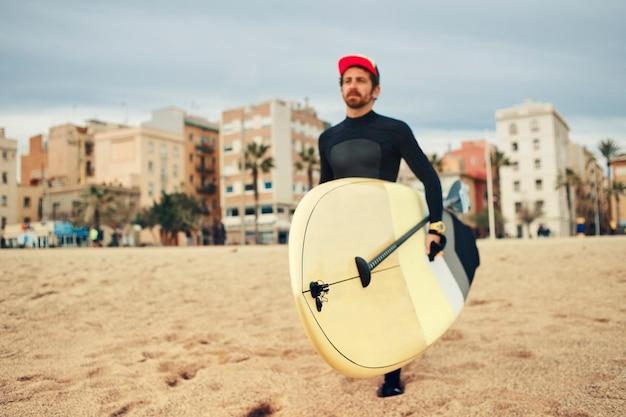 Młody surfer mężczyzna na plaży z deską surfingową