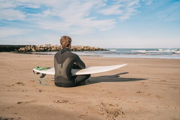 Młody surfer siedzi na piaszczystej plaży, patrząc na ocean z jego deską surfingową. koncepcja sportu i sportów wodnych.