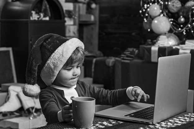 Młody święty mikołaj używa laptopa w swoim warsztacie. boże narodzenie