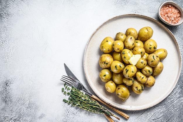 Młody świeże domowe ziemniaki gotowane z tymiankiem. białe tło. widok z góry. skopiuj miejsce.