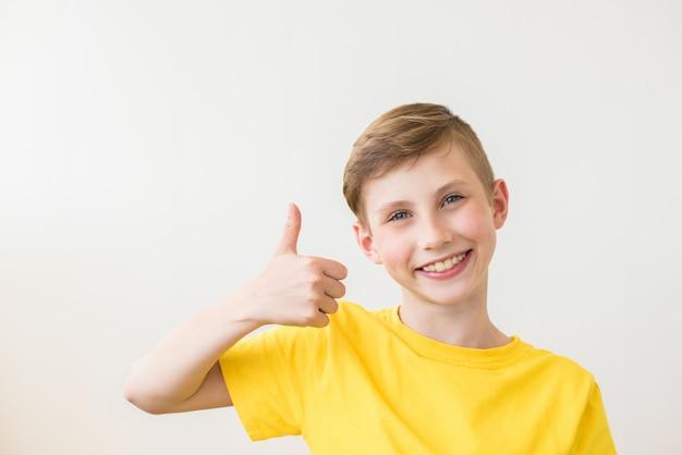 Młody świeży nastolatek pozuje z kciuka znakiem