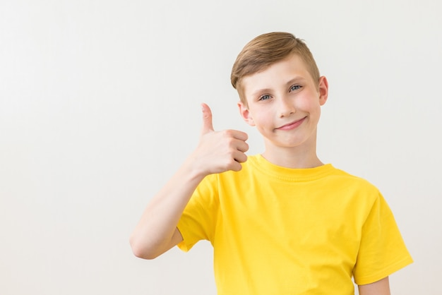 Młody świeży nastolatek pozuje z kciukiem do góry znak