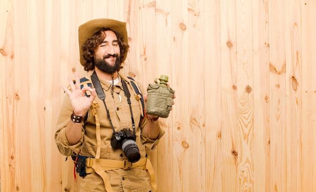 Młody szalony badacz z słomianym kapeluszem i plecakiem na drewnianym tle
