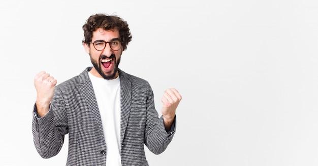 Młody szalony biznesmen czuje się szczęśliwy, zaskoczony i dumny, krzyczy i świętuje sukces z wielkim uśmiechem na ścianie