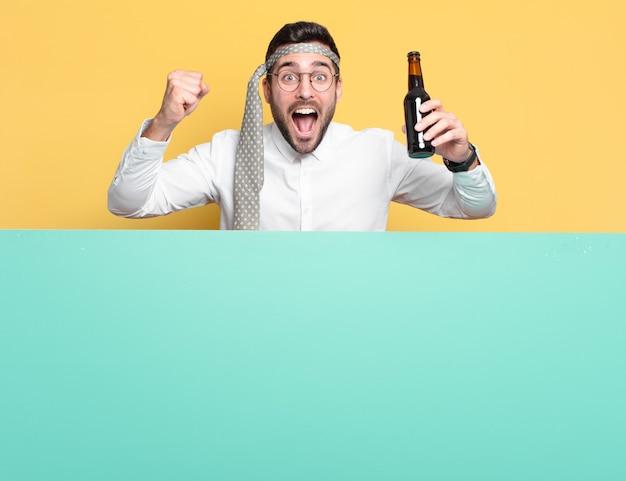 Młody szalony biznesmen z butelką piwa świętuje dobre wieści