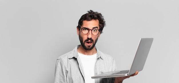 Młody szalony brodaty mężczyzna boi się lub zdezorientowany wyraz. koncepcja laptopa