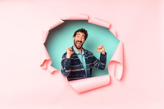 Młody szalony brodaty mężczyzna dumny i szczęśliwy wyrażenie. papierowa dziura pusta koncepcja tła