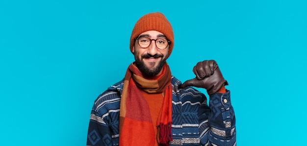 Młody szalony brodaty mężczyzna dumny z wyrazu twarzy i noszący zimowe ubrania