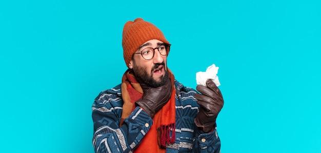 Młody szalony brodaty mężczyzna i noszenie zimowych ubrań. koncepcja choroby