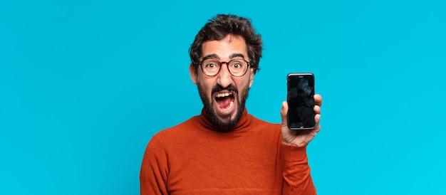 Młody szalony brodaty mężczyzna. koncepcja inteligentnego telefonu