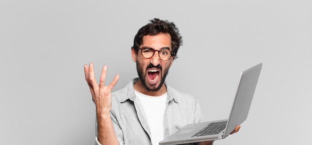 Młody szalony brodaty mężczyzna. koncepcja laptopa