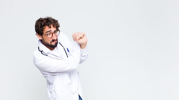 Młody szalony brodaty mężczyzna lekarz na ścianie przestrzeni kopii