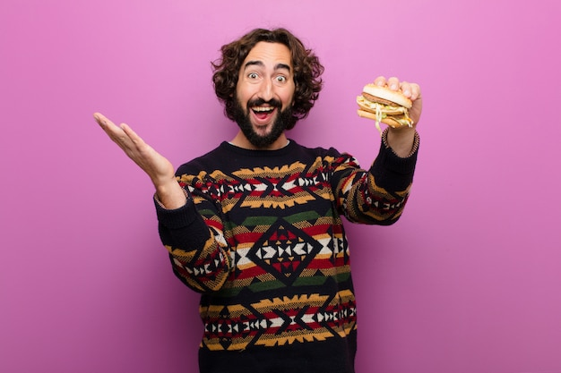 Młody szalony brodaty mężczyzna ma burgera