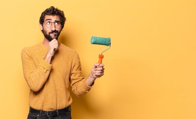 Młody szalony brodaty mężczyzna maluje wałkiem i zmienia kolor ściany