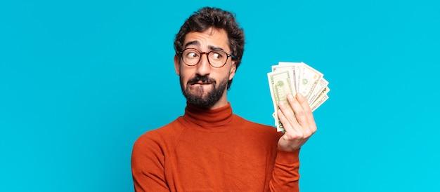 Młody szalony brodaty mężczyzna mylić wyraz. koncepcja banknotów dolarowych