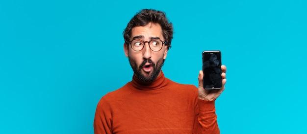 Młody szalony brodaty mężczyzna mylić wyraz. koncepcja smartfona