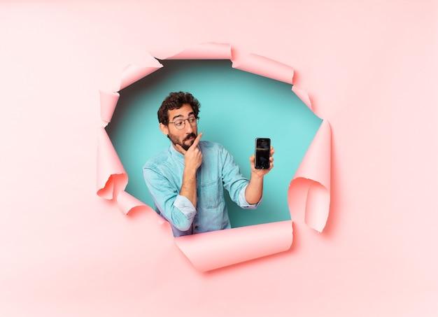 Młody szalony brodaty mężczyzna. myślenie lub wątpienie w exsion. koncepcja inteligentnego telefonu