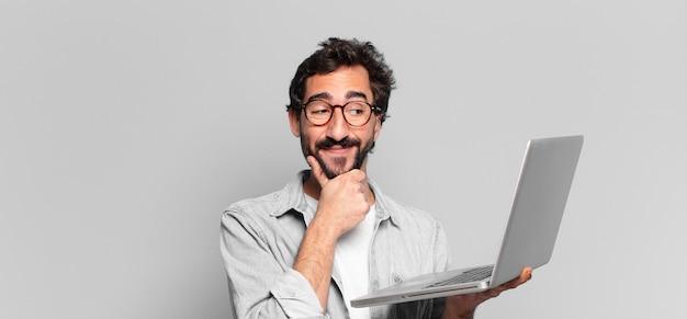 Młody szalony brodaty mężczyzna. myślenie lub wątpienie w exsion. koncepcja laptopa
