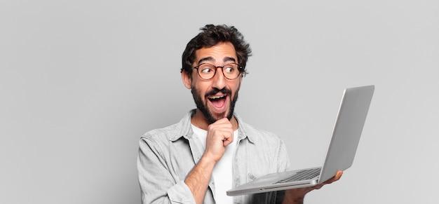 Młody szalony brodaty mężczyzna myśli lub wątpi w koncepcję laptopa ekspresji