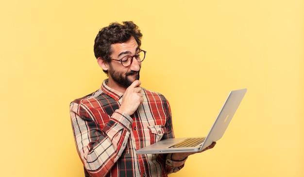 Młody szalony brodaty mężczyzna myśli wyrażenie i laptop