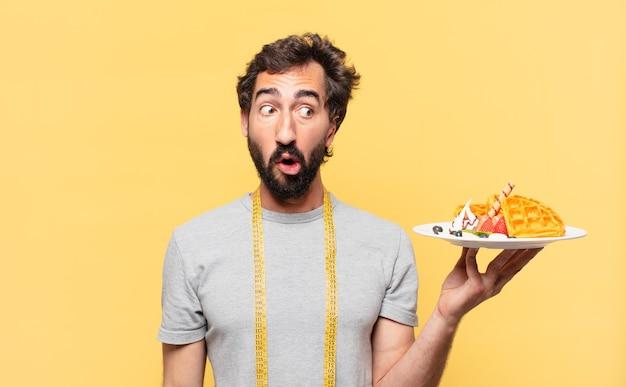 Młody, szalony brodaty mężczyzna na diecie, przestraszony wyraz twarzy i trzymający gofry