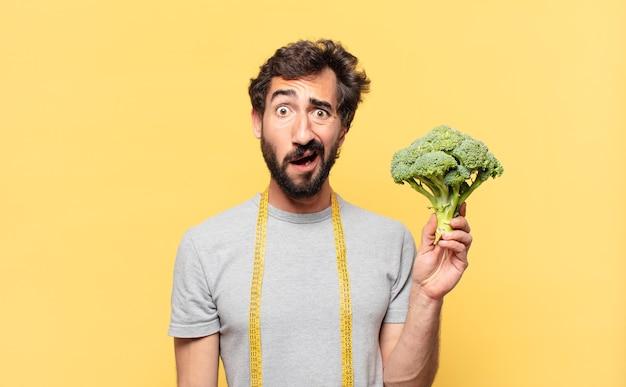 Młody szalony brodaty mężczyzna na diecie przestraszony wyraz twarzy i trzymający kapustę