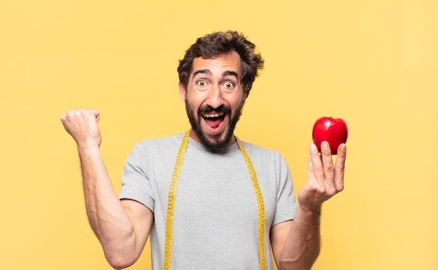 Młody szalony brodaty mężczyzna na diecie świętuje zwycięstwo i trzyma jabłko