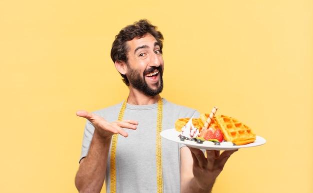 Młody szalony brodaty mężczyzna na diecie szczęśliwej i trzymającej gofry