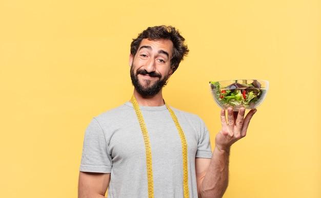 Młody szalony brodaty mężczyzna na diecie szczęśliwej wypowiedzi i trzymający sałatkę