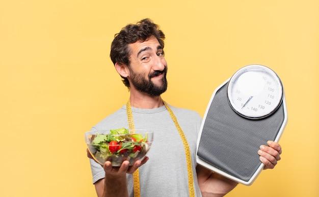 Młody szalony brodaty mężczyzna na diecie szczęśliwej wypowiedzi, trzymający wagę i sałatkę