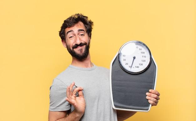Młody szalony brodaty mężczyzna na diecie, szczęśliwy wyraz twarzy i trzymający wagę