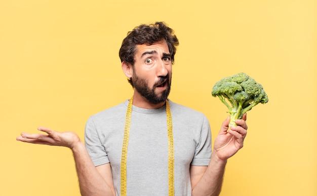 Młody szalony brodaty mężczyzna na diecie, wątpiący lub niepewny wyraz twarzy i trzymający kapustę