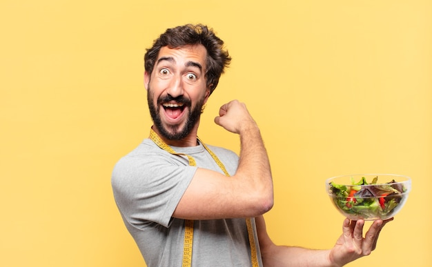 Młody szalony brodaty mężczyzna na diecie zaskoczony wyrazem twarzy i trzymający sałatkę