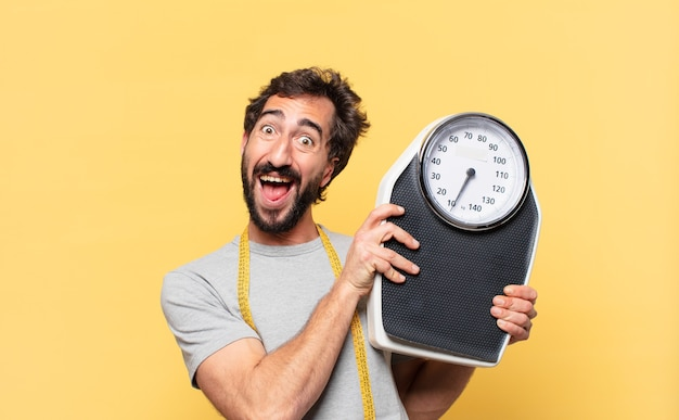 Młody szalony brodaty mężczyzna na diecie zaskoczony wyrazem twarzy i trzymający wagę