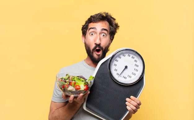 Młody szalony brodaty mężczyzna na diecie zaskoczony wyrazem twarzy, trzymający wagę i sałatkę
