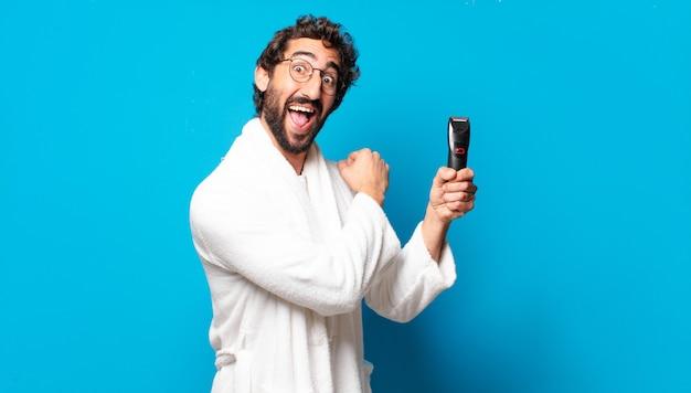 Młody szalony brodaty mężczyzna nosi szlafrok do golenia concep