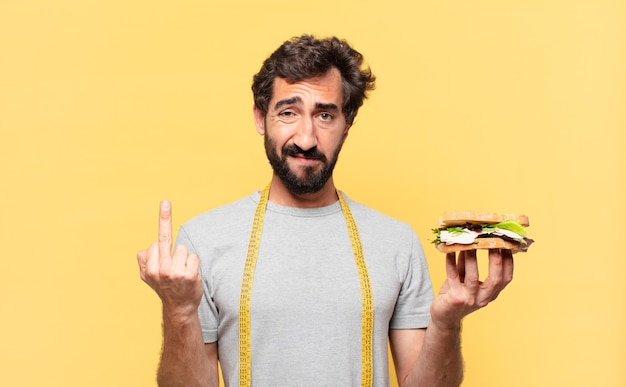 Młody szalony brodaty mężczyzna odchudzający się z gniewnym wyrazem twarzy i trzymający kanapkę