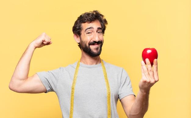 Młody szalony brodaty mężczyzna odchudzający się z uśmiechem na twarzy i trzymający jabłko