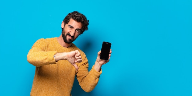 Młody szalony brodaty mężczyzna pokazuje ekran pustej komórki