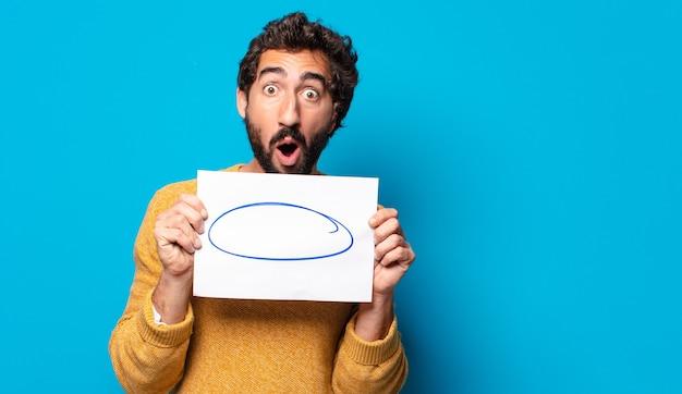Młody szalony brodaty mężczyzna pokazuje kartkę papieru z miejsca na kopię