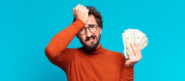 Młody szalony brodaty mężczyzna przestraszony wyrażenie. koncepcja banknotów dolarowych