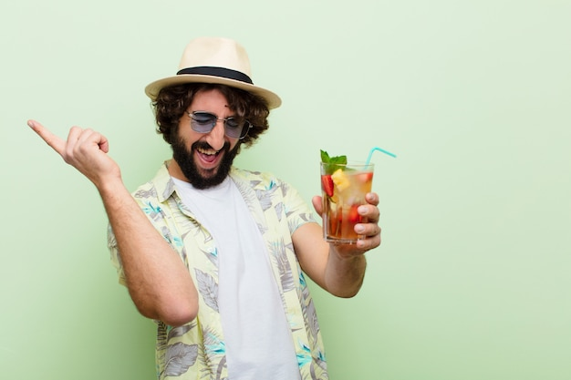 Młody szalony brodaty mężczyzna przy koktajlu. koncepcja turystyczna