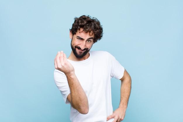 Młody szalony brodaty mężczyzna robi gest kapusty lub pieniędzy, każąc spłacić długi! o płaską ścianę
