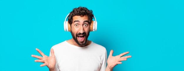 Młody szalony brodaty mężczyzna słuchający muzyki ze słuchawkami