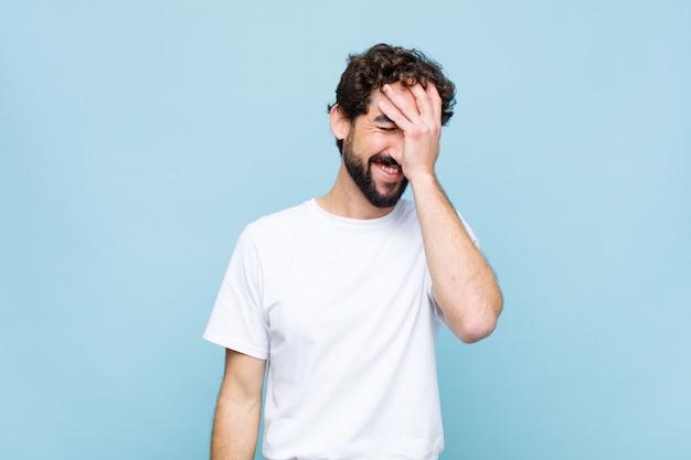 Młody szalony brodaty mężczyzna śmieje się i bije się w czoło. gest twarzy