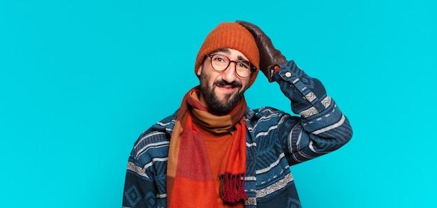 Młody szalony brodaty mężczyzna smutny wyraz twarzy i noszenie zimowych ubrań